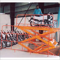 Track Hoist Hydraulic Power Scissor Lift Being Used For Loading Of Two Wheeler
